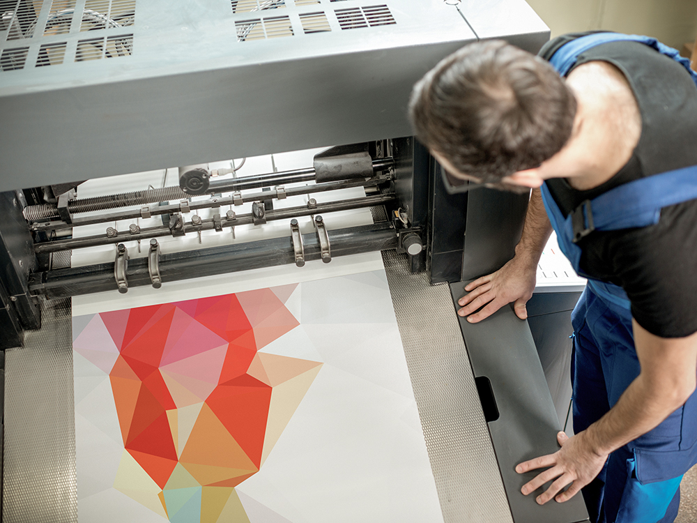 Worker following a printing process on the offset machine at the manufacturing