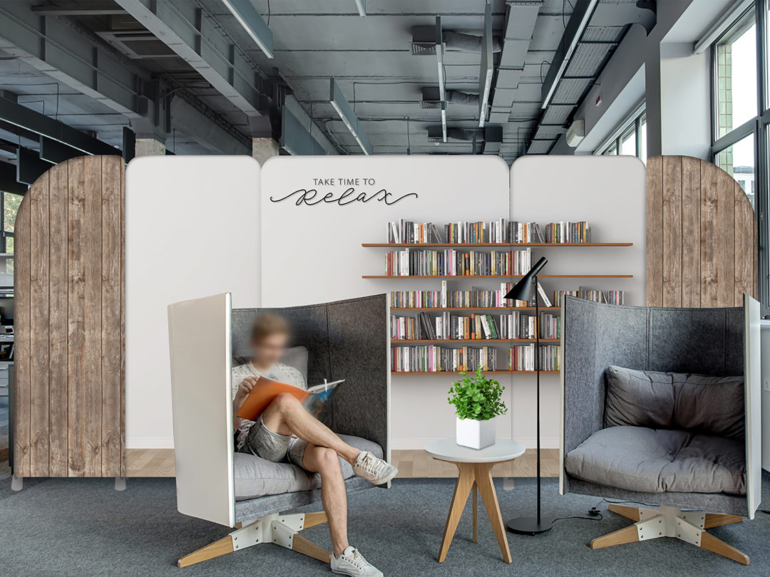 Relax zone in the coworking in a loft style with large windows and gray walls. There are fancy semi-rounded gray armchairs with pillows and a small round table with a black lamp between them.